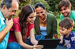 Three generation family using digital tablet in garden