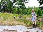 Girl looking at sheep on pasture