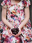 Girl holding cherries