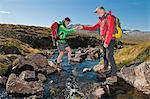 Mature hiking couple crossing river on rocks, Breidvik, Borgafjordur East, East Iceland