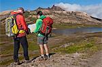 Mature hiking couple checking direction on map, Breidvik, Borgafjordur East, East Iceland
