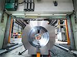Steelworker cutting steel on gantry milling machine in engineering factory
