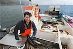 Fisherman gutting fish on boat