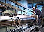 Engineer at lathe in engineering factory