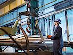 Engineer craning steel part onto lathe in engineering factory