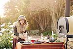 Mature hippy female preparing food on garden table