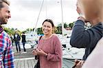 Happy woman talking to friends on pier