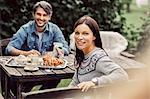 Portrait of happy couple having breakfast at organic farm