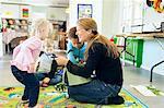 Full length of teacher giving toys to children