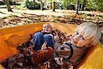 Two boys sitting in wheelbarrow full of leaves