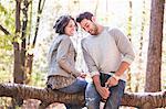 Couple sitting on fallen tree opening bottle of rose wine in forest
