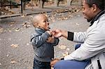 Male toddler fastening jacket zipper in park