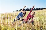Mature women practising yoga on field