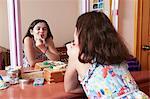 Girl applying lipstick in bedroom mirror
