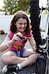 Laughing girl repairing bicycle on driveway