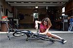 Girl repairing bicycle in front of garage