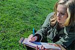 Teenage girl lying on grass writing in diary
