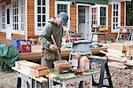 Mature man mixing wood varnish outside house