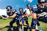 Teenage American football team defending on pitch