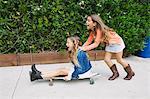 Girl pushing friend on skateboard