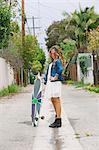 Girl standing in street holding skateboard