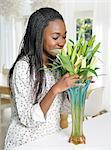 A woman arranging & smelling cut flowers