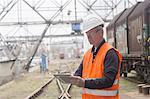 Dock worker using digital tablet at port