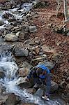 Hiker taking break by stream, Montseny, Barcelona, Catalonia, Spain