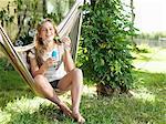 Teenage girl sitting on hammock, blowing bubbles