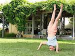 Girl doing headstand in garden