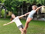 Two sisters doing acrobatics in garden