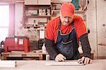 Cabinet maker checking blueprint at workshop bench