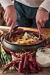 Person making potato salad, chili pepper in foreground
