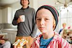 Portrait of boy eating cake in kitchen