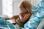 Female toddler sitting up in bed using digital tablet