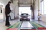 Full length of mechanic guiding car coming towards hydraulic lift