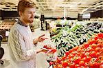 Young man buying fresh tomatoes at supermarket