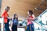 Three businesswomen having informal meeting at top of office stairs