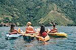 Rear view of four young female friends kayaking on Lake Atitlan, Guatemala