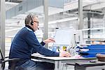 Mature man taking call at factory desk