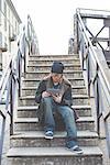Man using digital tablet on steps, Milan, Italy