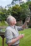 Senior man refilling bird feeder in garden