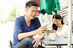 Tourist couple using smartphones at sidewalk cafe, The Bund, Shanghai, China