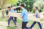 Volunteers carrying wood planks