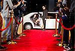 Bodyguard opening limousine for celebrity arriving at red carpet event