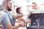 Barista steaming milk in cafe