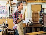 An antique furniture restorer in his workshop havng a coffee break.