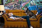 USA, Utah, Salt Lake City, Young man sleeping on sofa with dog, graffiti in background