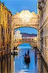 Italy, Veneto, Venice. Bridge of sighs illuminated at dusk with gondolas