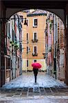 Italy, Veneto, Venice. Woman with red umbrella walking in the Castello quarter(MR)